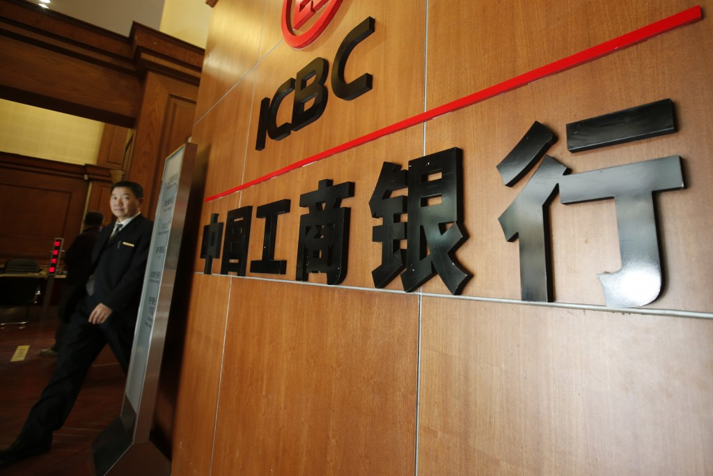 An employee of Industrial and Commercial Bank of China walks past a logo at an ICBC branch in Beijing