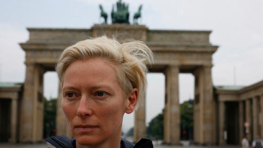 """Tilda Swinton fuhr 1988 mit dem Rad die Westseite der Berliner Mauer ab. Sie singt """"The wall, the wall – the wall must fall"""". Das Gorki Theater zeigt die Aufnahmen, die damals entstanden. © Sandro Kopp/Filmgalerie 451"""