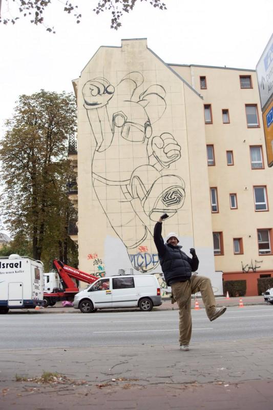 Elmar Lause posiert vor den ersten Wandskizze seines Murals in der Tornquiststraße © Affenfaust Galerie