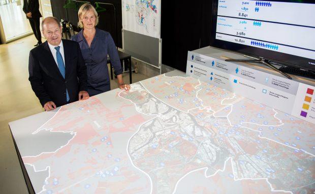 """Hamburgs Erster Bürgermeister Olaf Scholz (SPD) und Gesa Ziemer, Leiterin des """"CityScienceLab"""" stehen am 15.09.2016 in Hamburg im Rahmen einer Pressekonferenz, auf der die Ergebnisse des Projektes """"Finding Places"""" vorgestellt wurden, an einem an einem interaktiven Model. Mit dem Projekt """"Finding Places"""" soll nach freien Flächen für den Bau von Flüchtlingsunterkünften gesucht werden. Foto: Daniel Reinhardt/dpa +++(c) dpa - Bildfunk+++   Verwendung weltweit"""