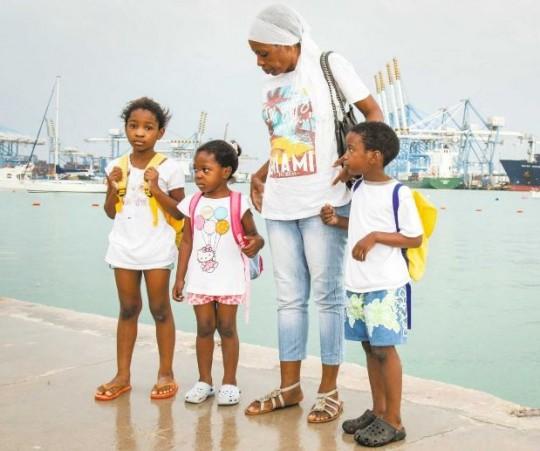 Paula, Victoria und Collins stehen mit ihrer Mutter an einem Hafen in Malta