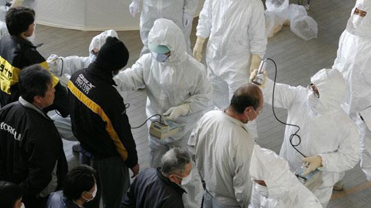 Kontaminierungsteams testen Flüchtlinge aus Fukushima auf Radioaktivität