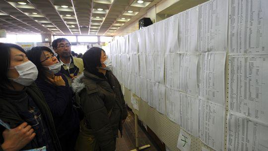 In einer Notunterkunft in der Stadt Natori durchsuchen Überlebende des Erdbebens Namenslisten nach Angehörigen.