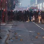 Eine Gruppe polnischer Polizisten steht randalierenden Neonazis gegenüber