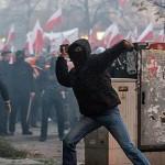 Ein vermummter Neonazi wirft einen Stein Richtung Polizei © Theo Schneider