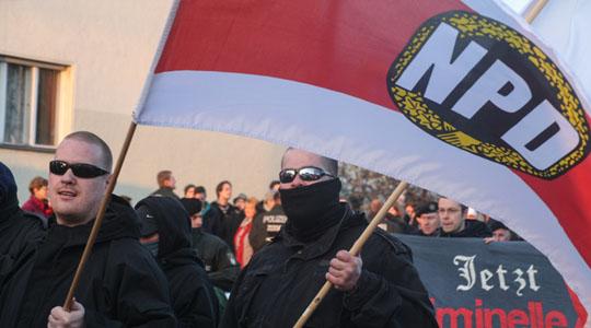 Ein NPD-Aktivist mit Fahne auf einem Aufmarsch in Berlin  © Theo Schneider