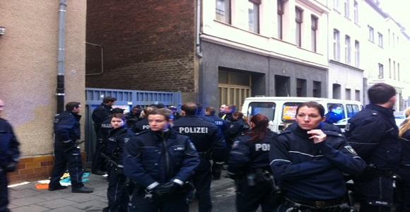 Polizeikette, um den Umgang mit einem Flüchtling im Hintergrund zu verdecken © Caro Lobig