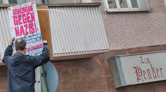 """Ein Aktivist befestigt vor der berüchtigten Neonazi-Kneipe """"Zum Henker"""" in Plakat für die Antifa-Demo am 30. April © Theo Schneider"""