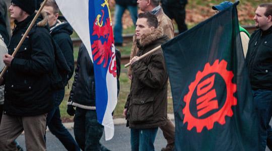 Ein Neonazis trägt während des Aufmarsches eine Fahne der tschechischen DM (Dĕlnická mládež) © Theo Schneider