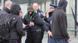 Der vermummte Berliner Neonazi Tim W. im Gerangel mit Polizisten in Weimar © Red Foxx Fotografie