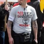 Ein tätowierter Neonazi-Ordner mit rechten Parolen auf dem Shirt © Theo Schneider