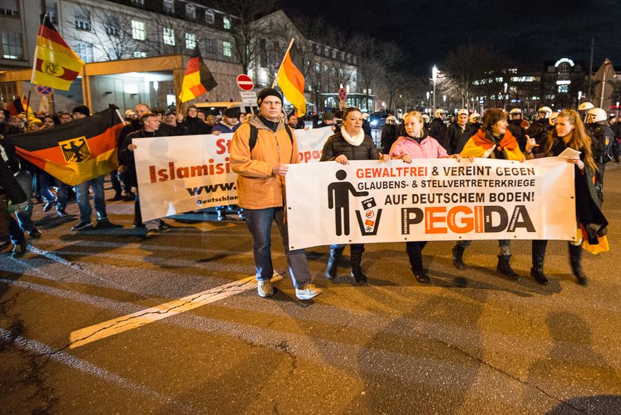 Thomas Rettig, Anmelder der Pegida-Kundgebung und letztjähriger AfD-Kandidat hinter dem Fronttransparent des Pegida-Aufmarsches (mit orangefarbener Jacke) | © Christian Martischius