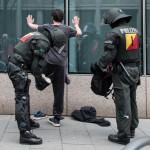 Polizeibeamte durchsuchen einen Gegendemonstranten | © Christian Martischius
