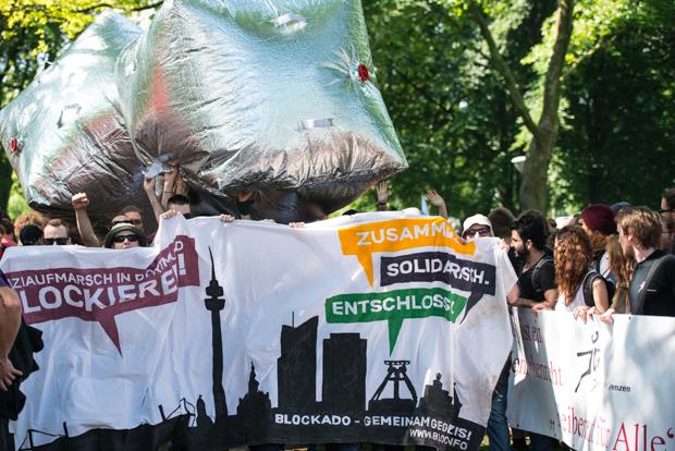 Aktivisten des BLOCKADO-Bündnisses mit Transparent und Spiegelwürfeln | © Christian Martischius