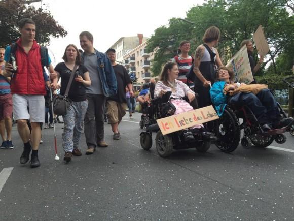 Rollstuhlfahrerin mit Plakat Ich liebe das  Leben