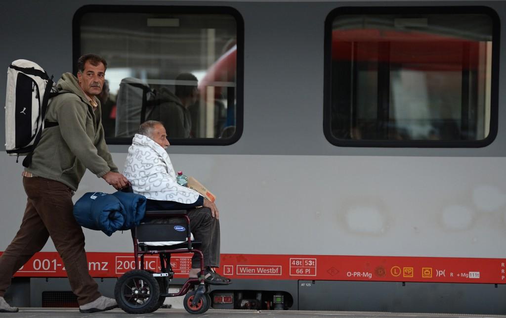 Ein Flüchtling schiebt am 06.09.2015 bei der Ankunft am Hauptbahnhof in München (Bayern) einen älteren Mann, der im Rollstuhl sitzt, über den Bahnsteig zu einem anderen Zug. Foto: Andreas Gebert/dpa +++(c) dpa - Bildfunk+++