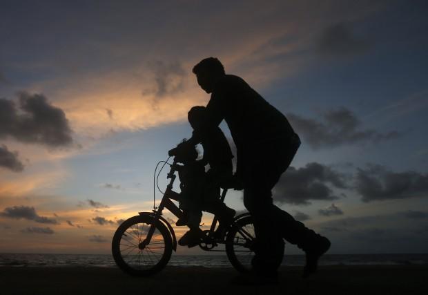 Ein Vater mit seinem Kind am Strand. © Dinuka Liyanawatte / Reuters